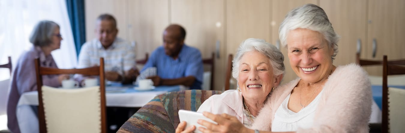 smiling senior woman taking selfie with friend