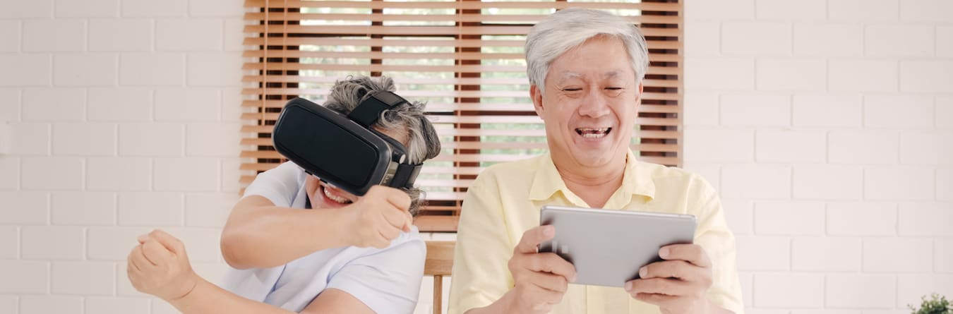 Asian Elderly Couple Using Tablet And Virtual Reality Simulator