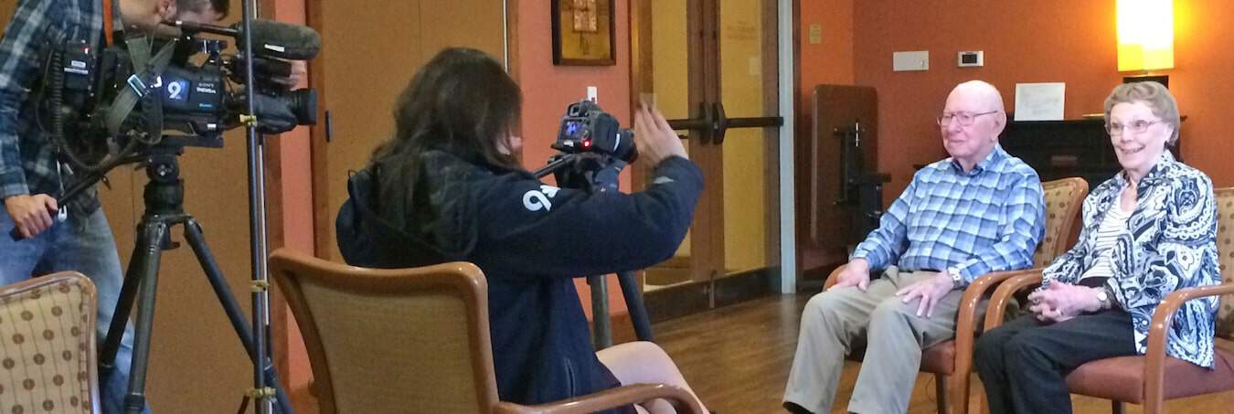 Videographer taping a senior couple in interview style