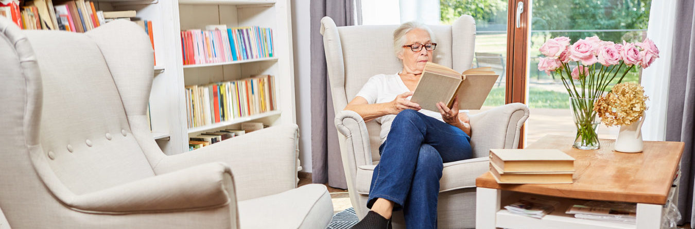 Elderly Woman sitting in chair reading