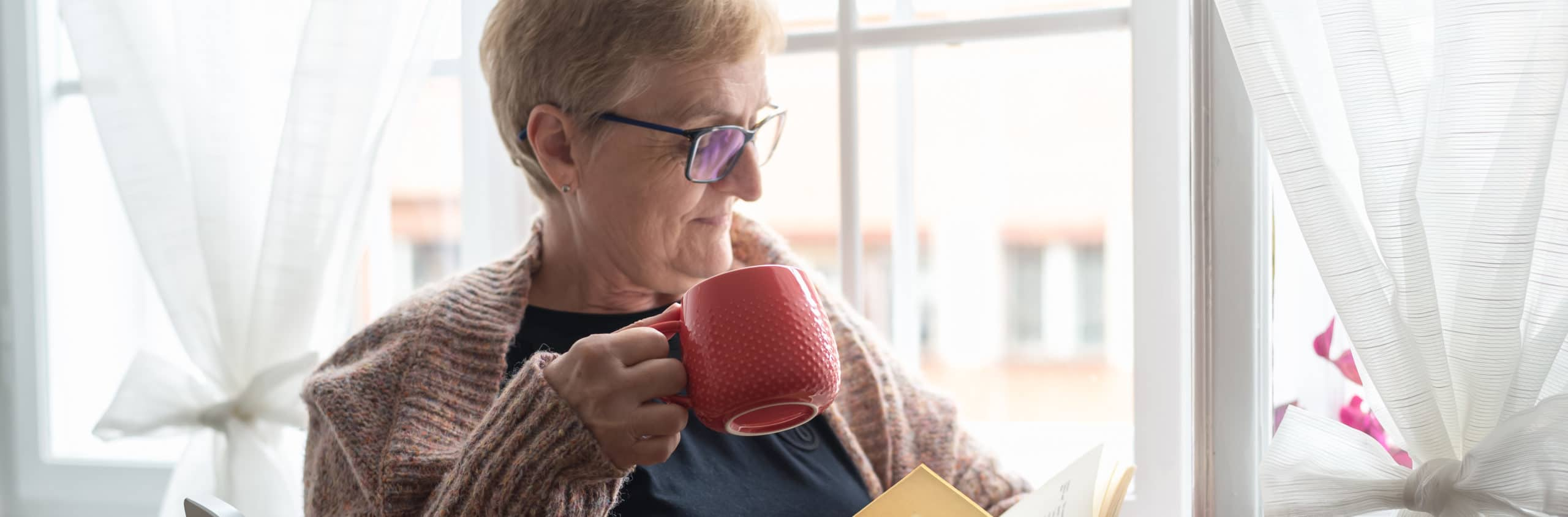 elderly woman reading book while sipping tea